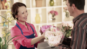 Blog post image for LA Biz Guide. It is a florist interacting with a customer. This blog post talks about the top 5 reasons to support small businesses.